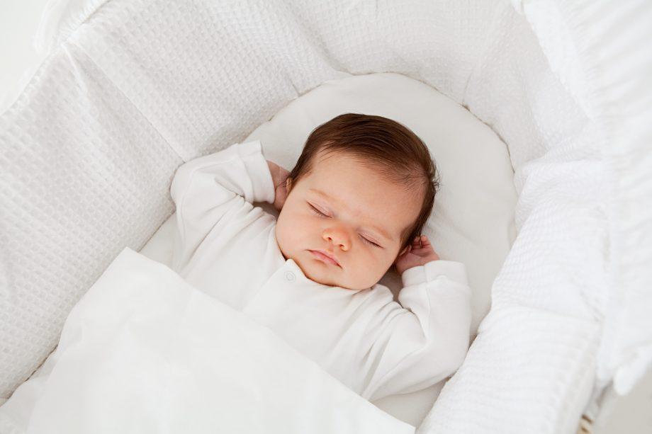 sleeping baby in Moses basket