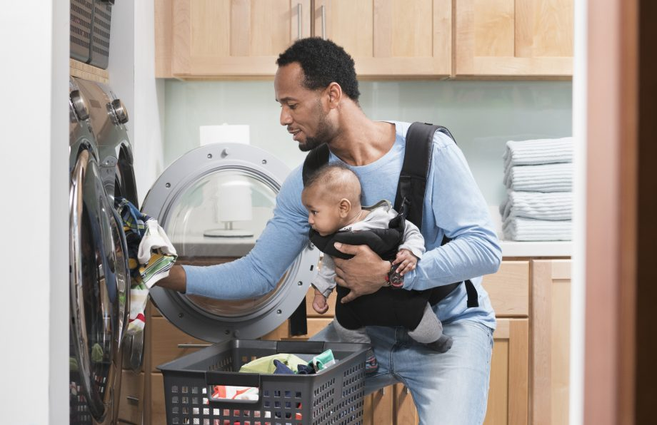 father with son in baby carrier doing laundry