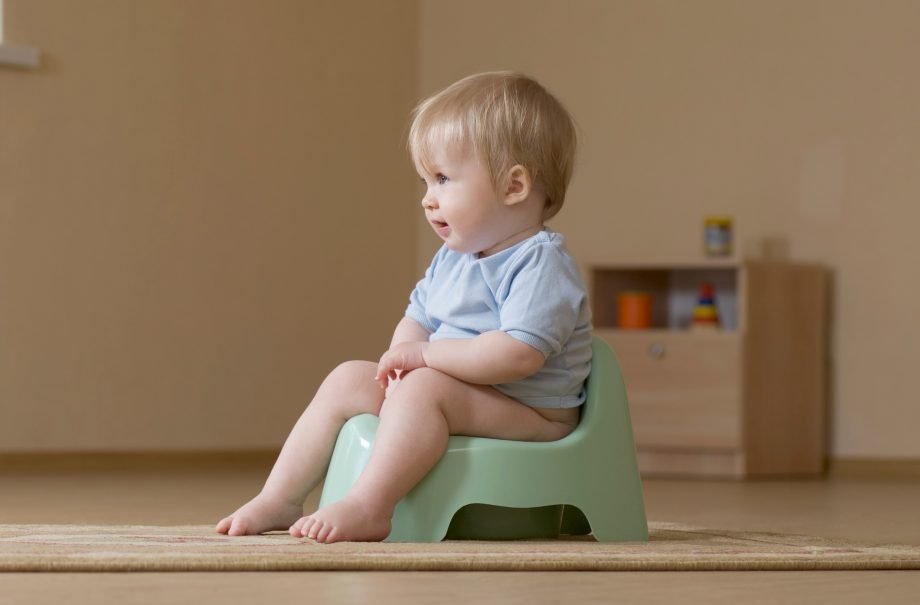 A child potty training and looking off camera to parents learning how to potty train.