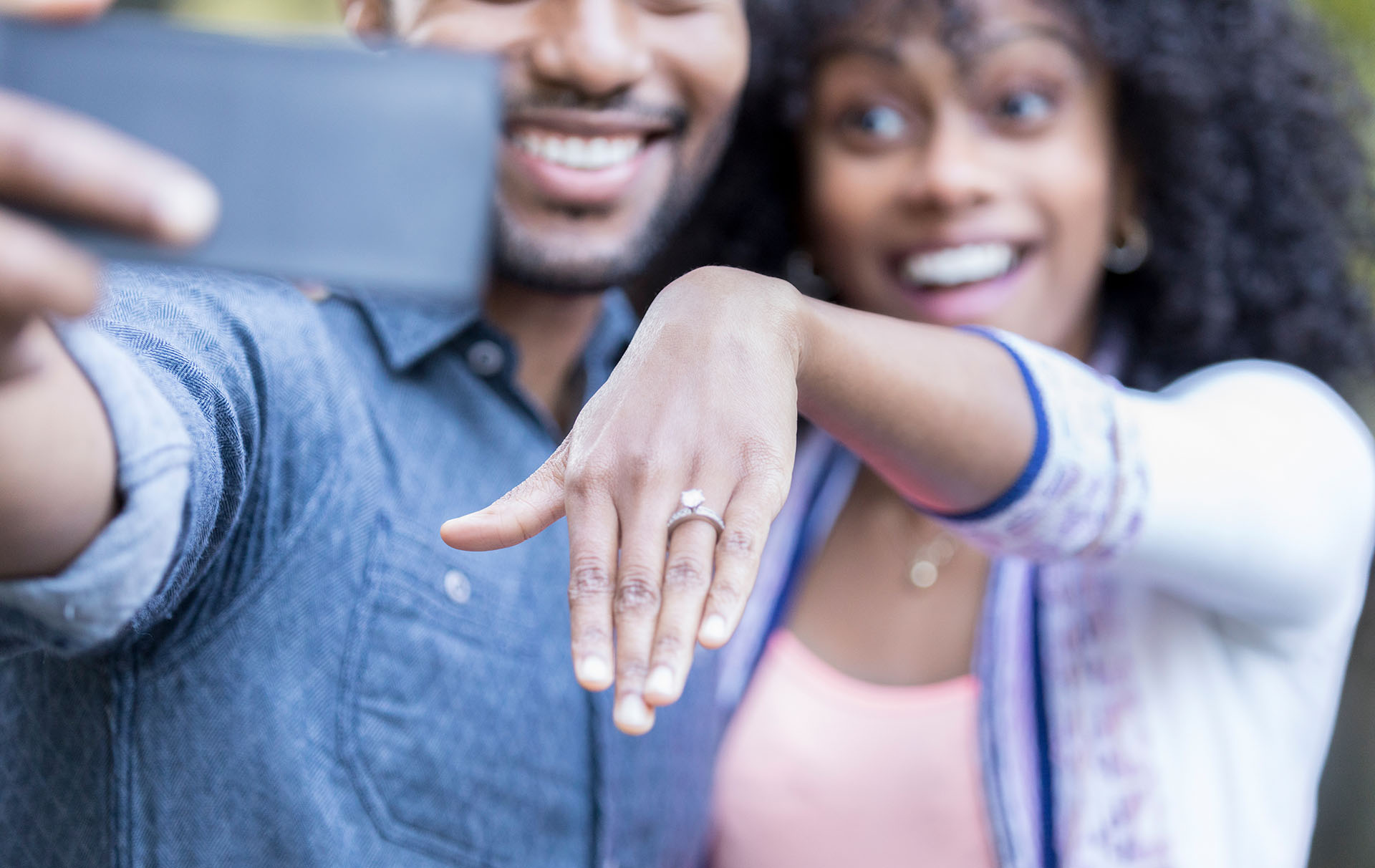 woman uses cousin's hand in engagement photo