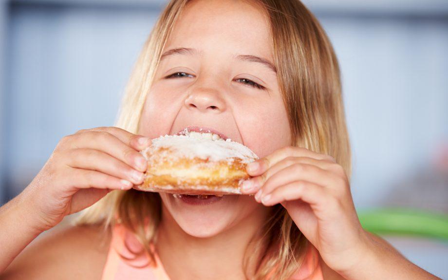 child eating doughnut: daily sugar allowance