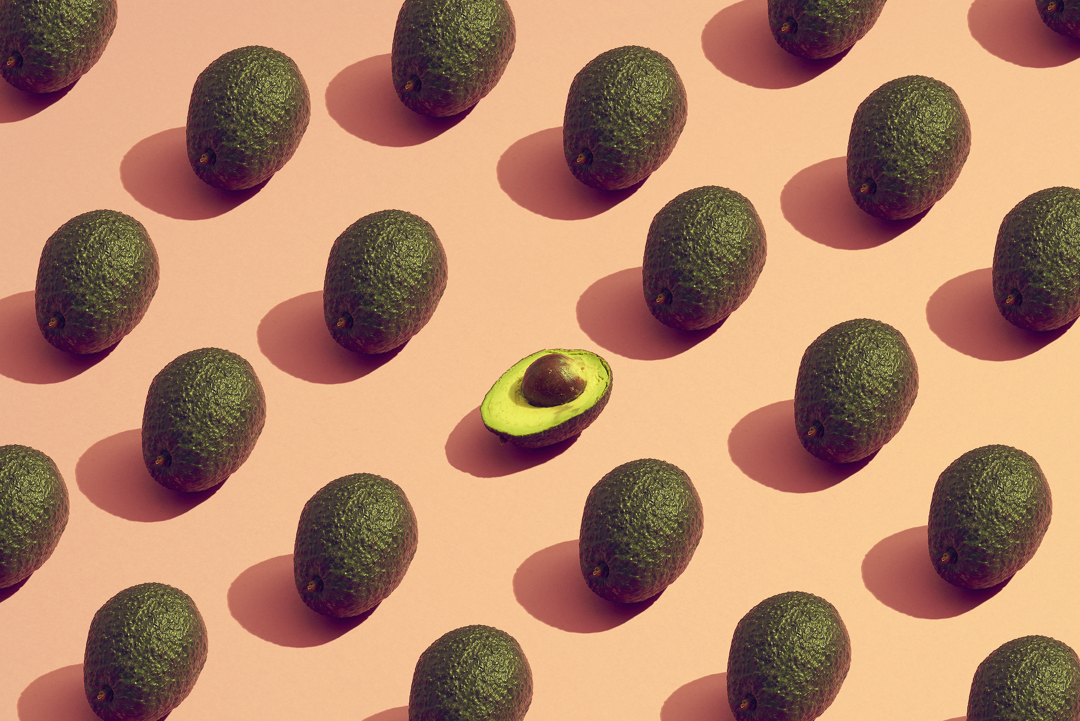 Th benefits of avocado shown in a pattern made from avocados.