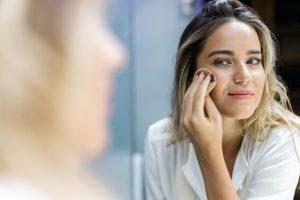 femme appliquant son maquillage avec de l'huile bio