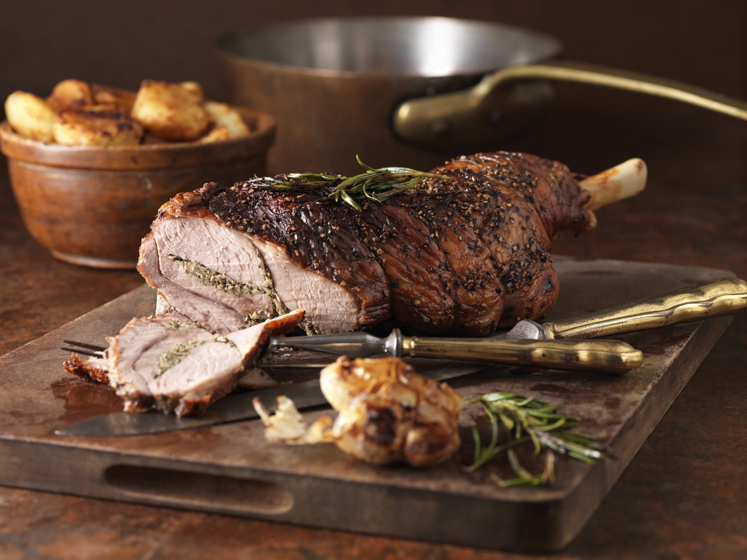 Easter dinner on a plate with rosemary and garlic leg of lamb and roast potatoes