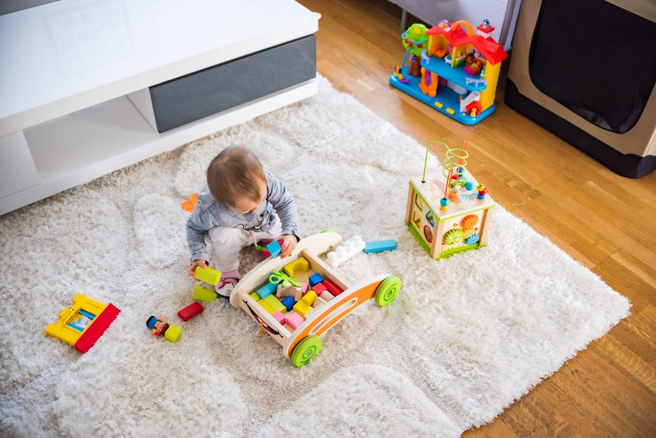 Baby playing on a mat amongst toys for one year olds
