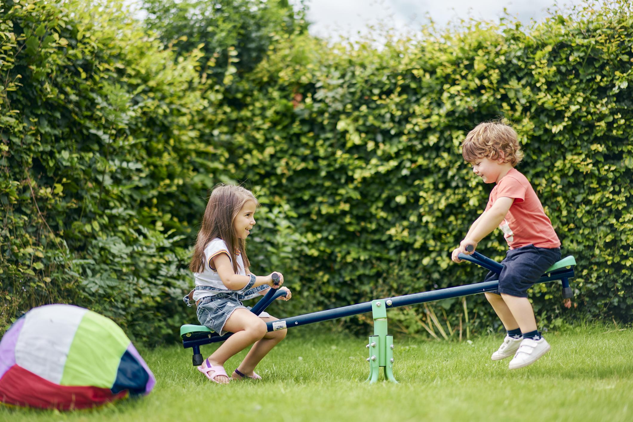 Enfants de quatre ans jouant ensemble dans le jardin