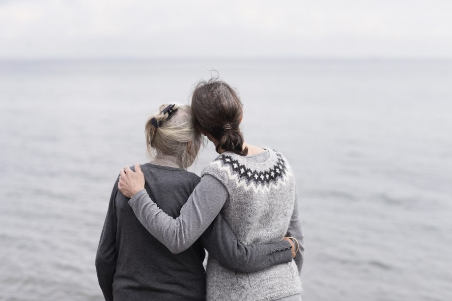 Two women of different ages hugging while looking out over a grey sea.