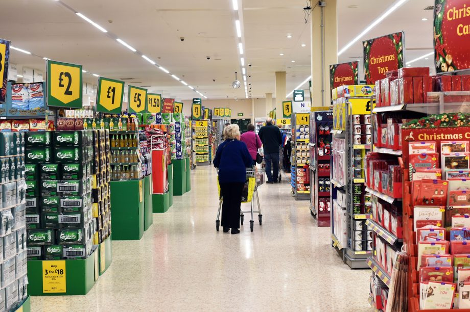 When is the best time to do Christmas food shopping? Large Aisle of a supermarket at Christmas with special offers on the end aisles.