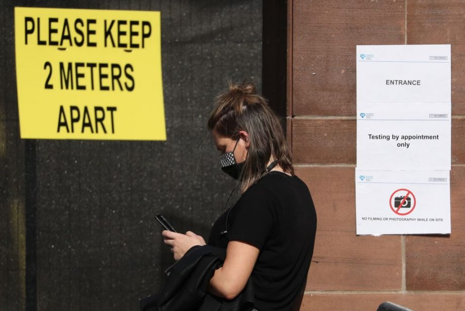 A member of the public queues by a sign reading