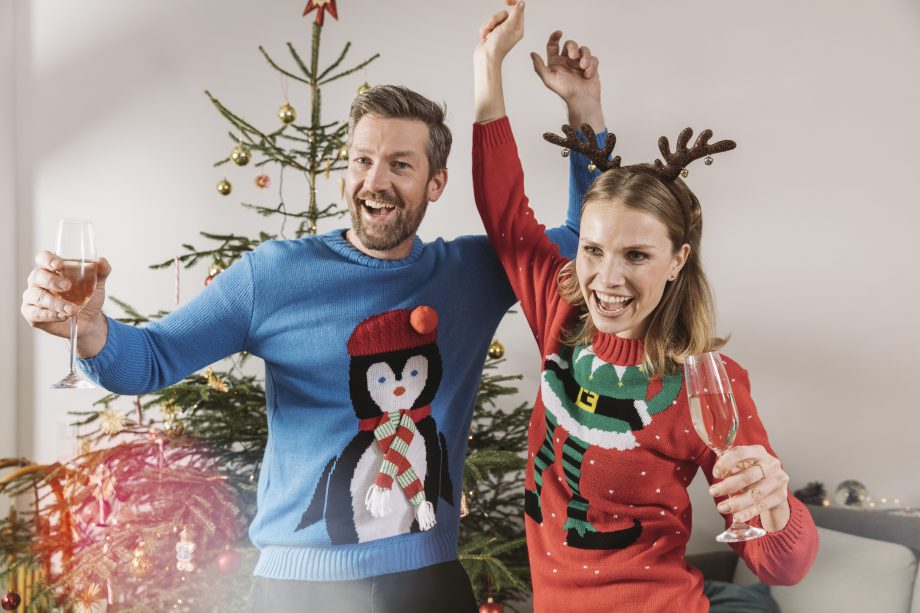 A man and a woman wearing traditional Christmas jumpers