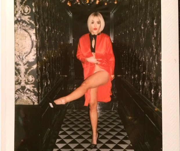 Rita poses for Paper magazine in a hot red Dior coat and little else...